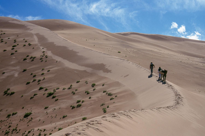 Hikers climbing Khongoryn Els dunes Mongolia